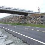 Stor blokk i B-kvalitet brukt i ein forstøtningsmur  på Os-vegen i Hordaland