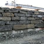 Stor blokk i B-kvalitet brukt i ein forstøtningsmur.