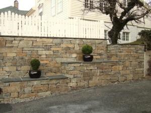 Ved dette hageanlegget på Lofthus i Ullensvang er det nytta handstein av A-kvalitet  saman med hyller av skifer. Det bryt opp fasaden og gjev eit vakker og praktisk uttrykk.